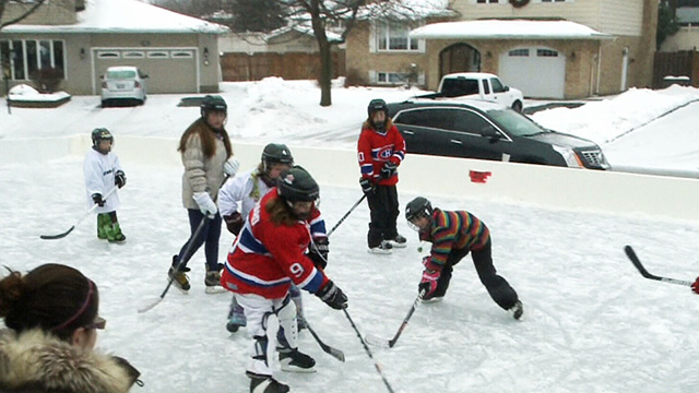 Kids playing hockey in front of the house