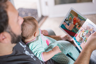 A father reading a book to a baby