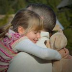 A young girl is giving a hug to her father