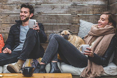 Two people are relaxed with a dog in a cabin