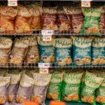 A shelf full of potato chip bags