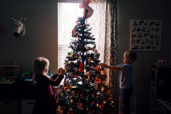 A boy and a girl decorating a Christmas tree