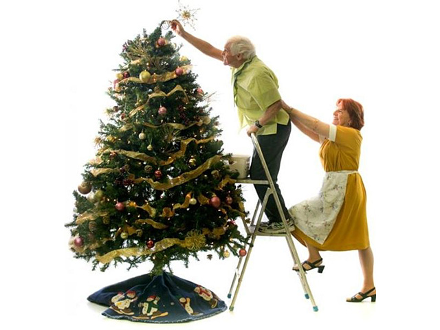 old man putting a star on the tree