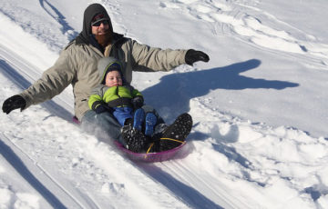 sledding dad and a boy