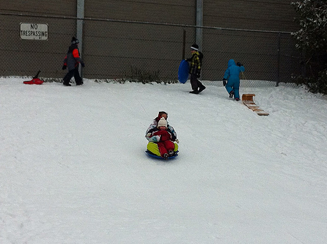 kids sledding on the slope