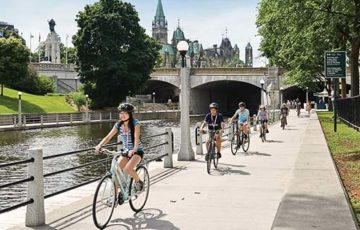people are cycling along the canal