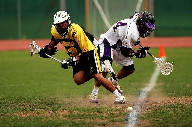 two guys  are playing lacrosse