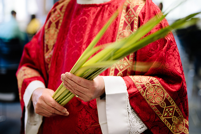 A priest holding a palm leaf